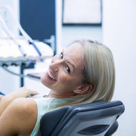 Lady in the dentist chair looking over her shoulder and smiling