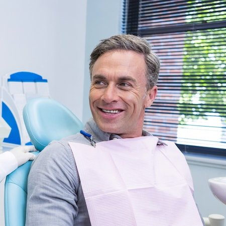 Older gentleman with grey hair in the dentist chair and smiling