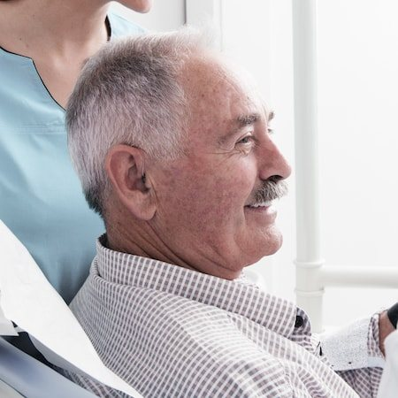 Side-on view of an older male patient smiling in the dentist chair
