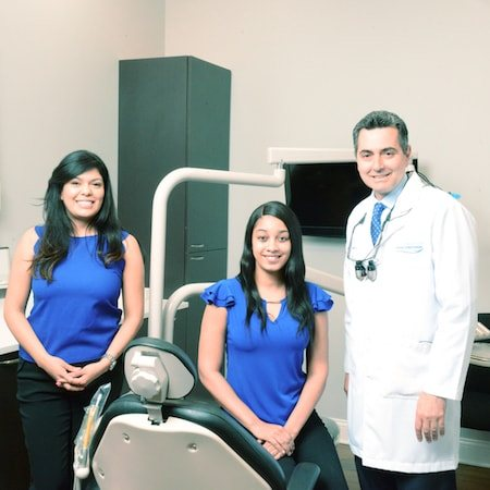 Dr. Katris wearing his lab coat and smiling with two of our dental hygienists in a treatment room
