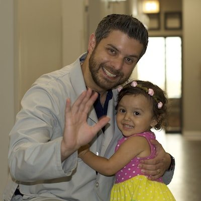 Dr. Kuttab waving and hugging a young patient