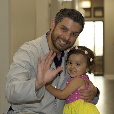 Dr. Kuttab hugging a little female patient after her pediatric care