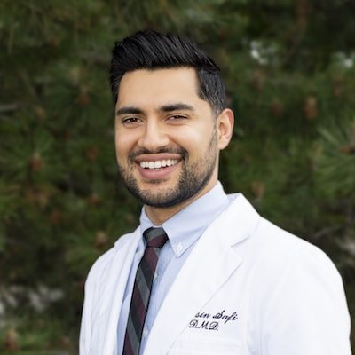 Dr. Safi smiling while wearing his dentist coat and standing outside