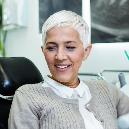 Female patient with short white hair looking down and smiling