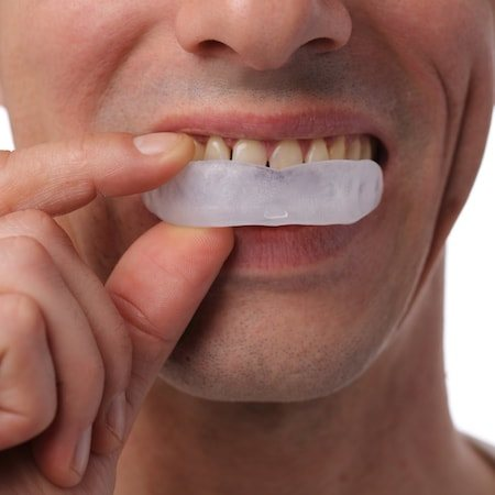 Close-up of a man placing a mouthguard over his teeth