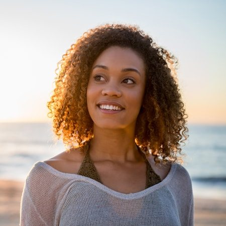 Lady with frizzy hair standing in front of a beautiful sunset on the beach