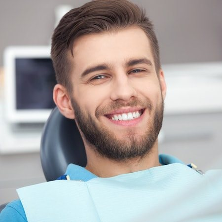 Young male patient with a beard wearing a dental bib and smiling