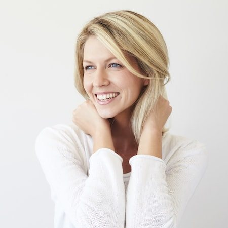 Blonde lady with both hands on the back of her neck and smiling