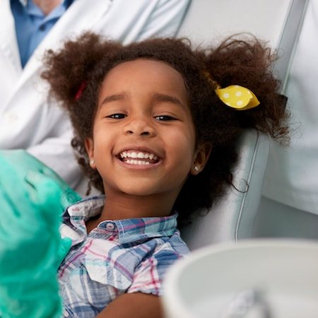 Little girl sat in the dentist chair laughing