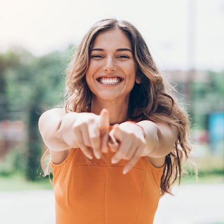 Woman smiling and pointing forward with both hands on a sunny day