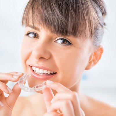 Woman smiling holding Invisalign clear aligners from Carol Stream and Elgin Dental Associates